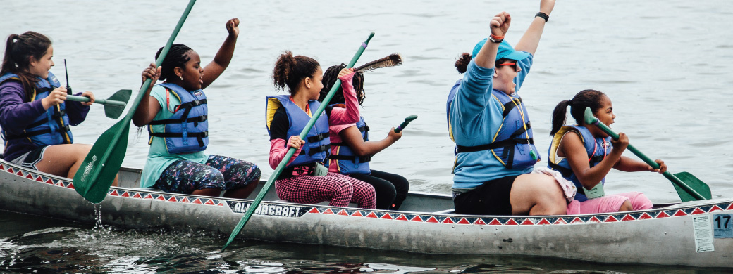 Campers and their Spark Champion celebrate after winning a canoe race