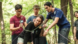 Teens make their way through a team-building obstacle course